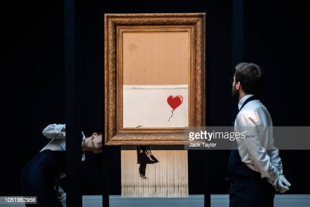 Sotheby's employees view 'Love is in the Bin' by British artist Banksy during a media preview at Sotheby's auction house on October 12 2018 in London...
