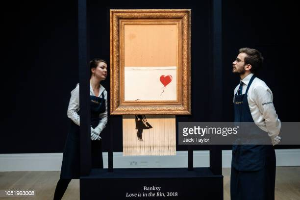 Sotheby's employees view 'Love is in the Bin' by British artist Banksy during a media preview at Sotheby's auction house on October 12, 2018 in...