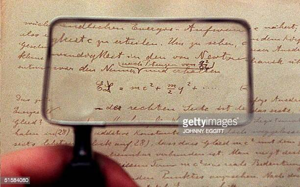 Sotheby's expert holds a magnifying glass up to the earliest surviving Einstein manuscript on relativity 04 March The manuscript will be auctioned 16...