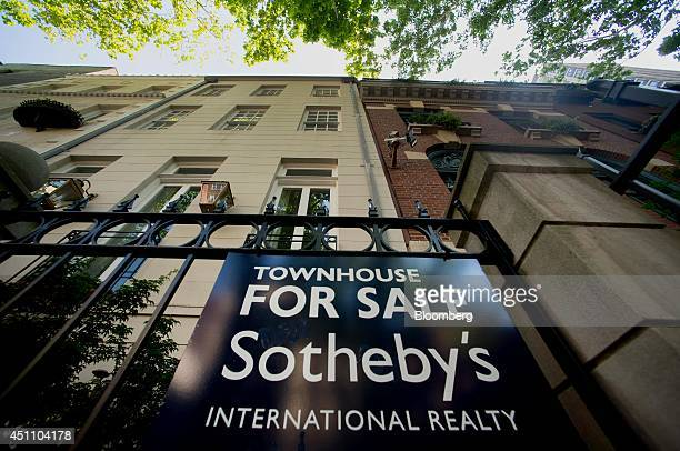 A Sotheby's 'For Sale' sign is displayed outside of a townhouse in New York US on Monday June 23 2014 Americans snapped up previously owned homes in...