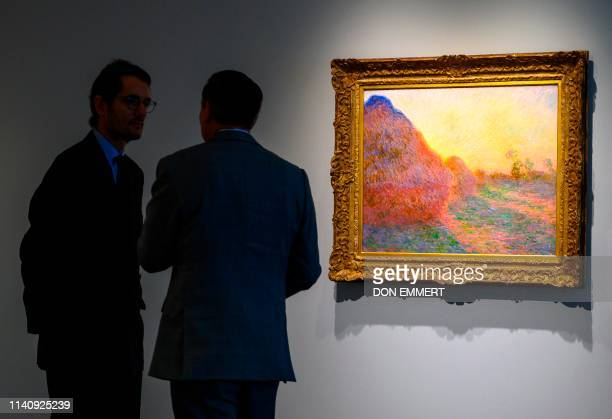 Sotheby's officials stand near one of Claude Monet's Meules during a media preview for Sotheby's Impressionist Modern Art and Contemporary Art...