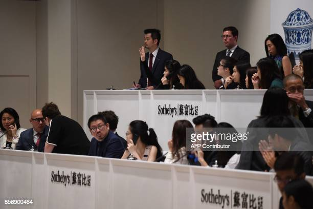 A Sotheby's phone auctioneer raises her hand to indicate taking the final bid for the record breaking sale of a Ru Guanyao brush washer bowl from...