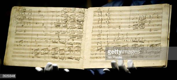 Sotheby's porter holds the manuscript for Ludwig van Beethoven's first edition of the Ninth Symphony as it goes under auction May 22 2003 in London...