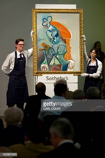Sotheby's staff hold the Pablo Picasso painting entitled 'Buste De Matador' as it is auctioned at Sotheby's in London on June 22 2010 where it...