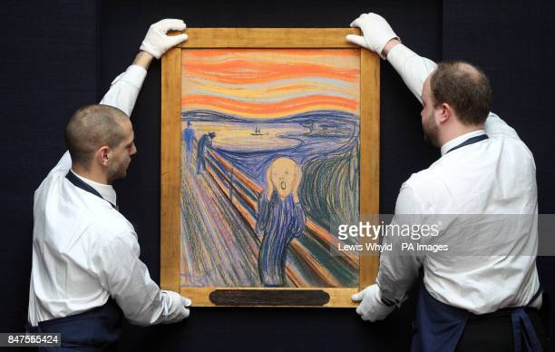 Sotheby's staff members hang The Scream, by Norwegian painter Edvard Munch before being shown at the auction house's central London offices.