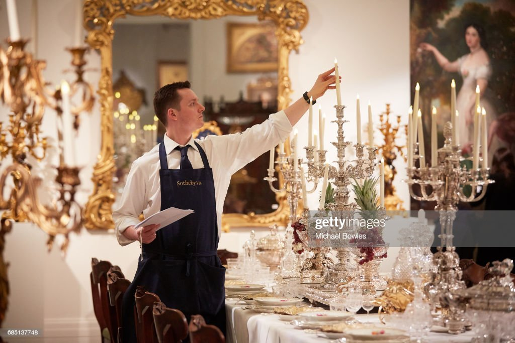A Sotheby's technician adjusts a candelabra on display as part of the Ballyedmond Collection at Sotheby's on May 19, 2017 in London, England.