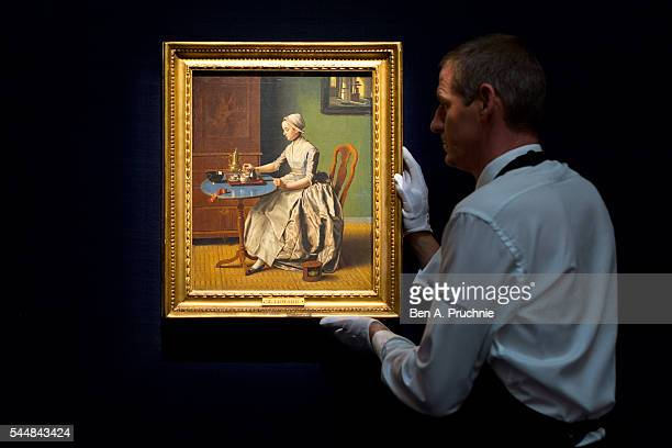 Sotheby's technician adjusts A Dutch Girl at Breakfast by JeanEtienne Liotard at Sotheby's London on July 1 2016 in London England A highlight of the...
