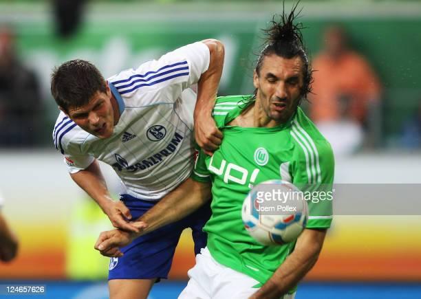Sotirios Kyrgiakos of Wolfsburg and KlaasJan Huntelaar of Schalke battle for the ball during the Bundesliga match between VfL Wolfsburg and FC...