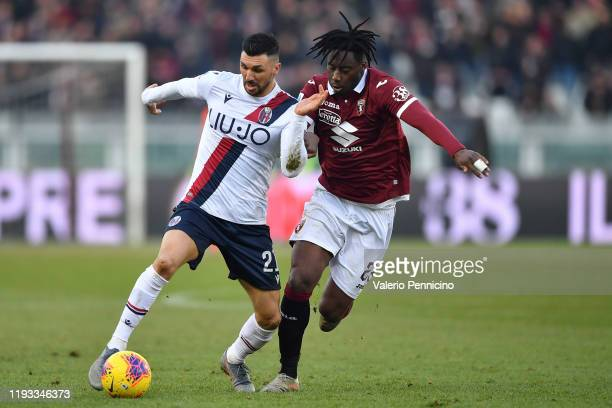 Soualiho Meite of Torino FC competes with Roberto Soriano of Bologna FC during the Serie A match between Torino FC and Bologna FC at Stadio Olimpico...