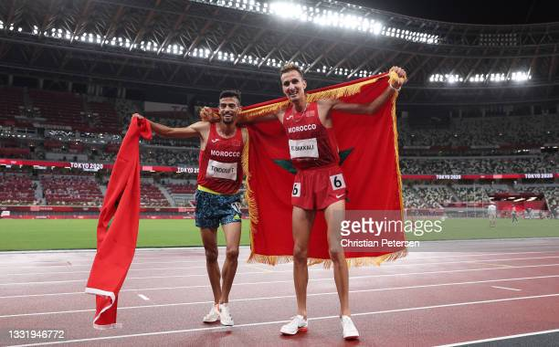 Soufiane El Bakkali of Team Morocco celebrates with teammate Mohamed Tindouft on track with their countries flag after winning gold in the Men's 3000...