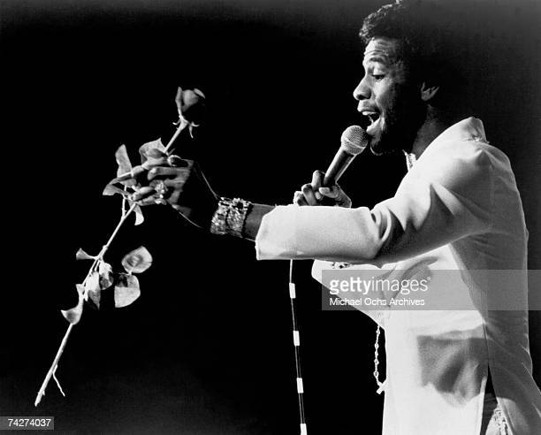 Soul singer Al Green performs onstage holding a rose in circa 1974.