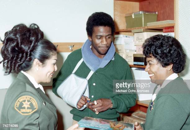 Soul singer Al Green signs an autograph for a female Los Angels County sheriff's deputy on February 6, 1974 in Los Angeles, California.