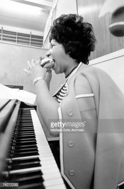 Soul singer Aretha Franklin enjoys a hamburger while sitting at the piano in the Atlantic Records studio during 'The Weight' recording sesssion on...