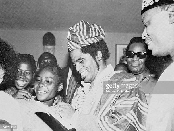 Soul singer James Brown visits Africa and signs autographs wearing traditional native garb in 1974