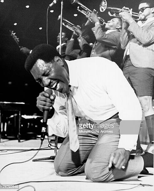 Soul singer Otis Redding passionately gets down on his knees with his horn section behind him as he performs onstage in 1967