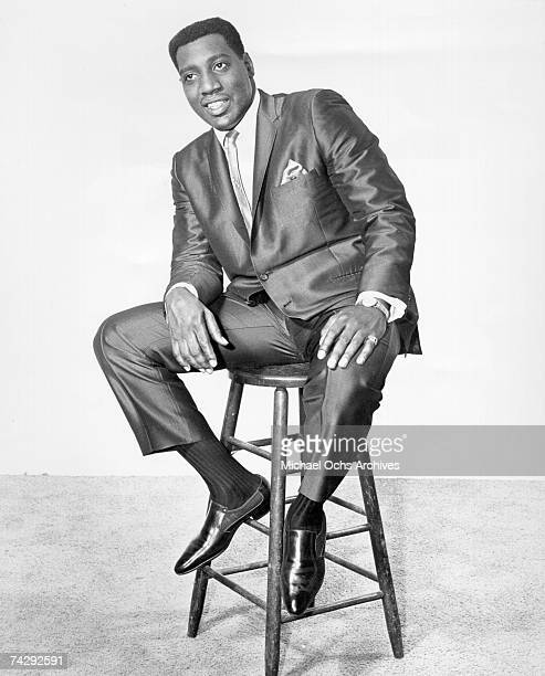 Soul singer Otis Redding poses for a full length portrait sitting in a chair in 1965