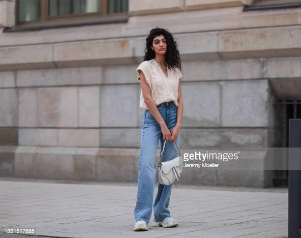 Soulin Omar wearing white Balenciaga triple s sneakers, white Dior Saddle bag, beige Mango top, Zara blue jeans and Christ jewelry on July 27, 2021...