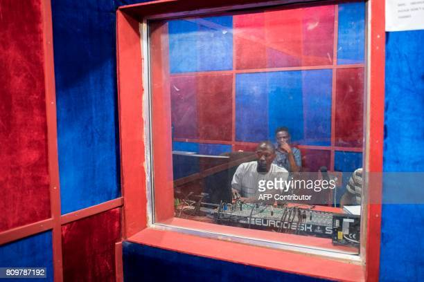 Sound engineer and a presentor take part in a live broadcast at the University of Maiduguri radio station, in Maiduguri, on July 4, 2017. The...
