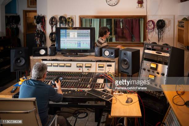 sound engineer and musician preparing for recording session in studio - audio equipment stock pictures, royalty-free photos & images