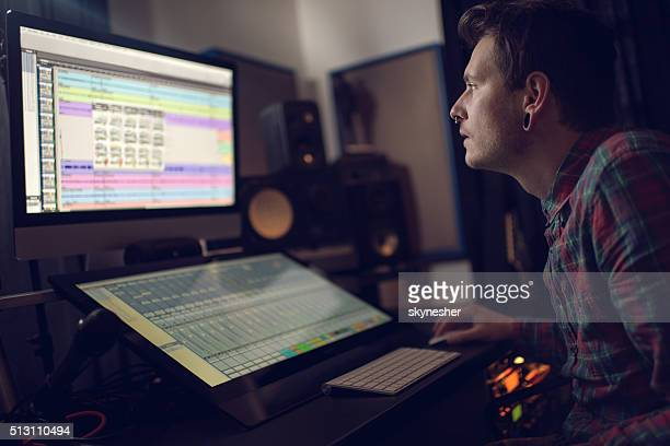 Sound engineer using computer in recording studio.