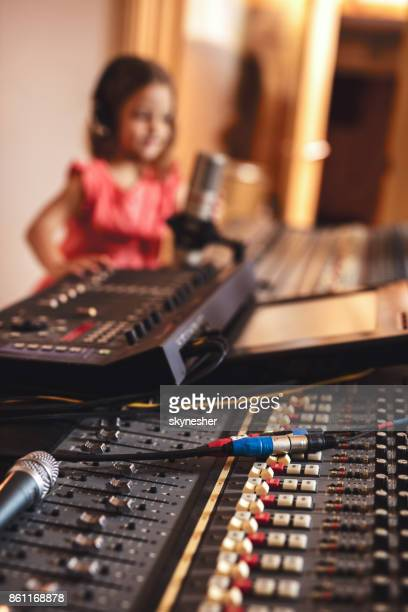 Sound mixer in radio station with girl in the background.