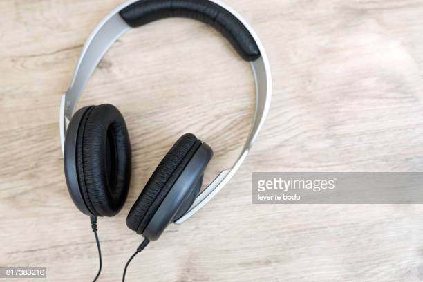 Sound music headphone (earphone) Stereo volume equipment object. Closeup photo of headphones on wooden background and copyspace area for a text. Audio technology, gadgets and music concept.