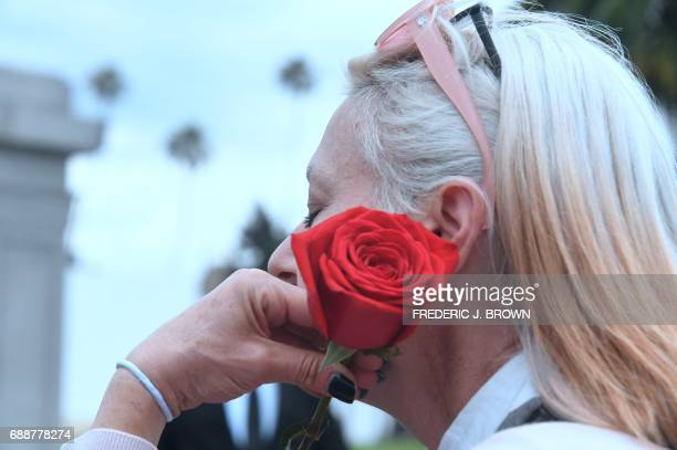 Soundgarden fan Stephanie Sellnau who came down from San Francisco holds a rose while grieving the loss of Soundgarden frontman Chris Cornell at his...