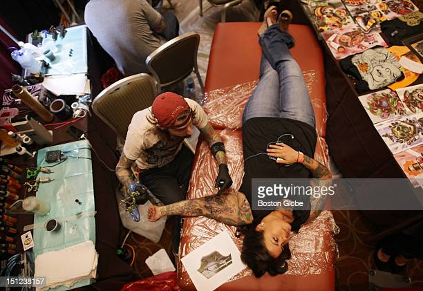 Sounds of buzzing tattoo machines fill the Grand Ballroom of the Sheraton Hotel in Back Bay as Timmy B works on a tattoo for Gina Malloy of Keen NH...