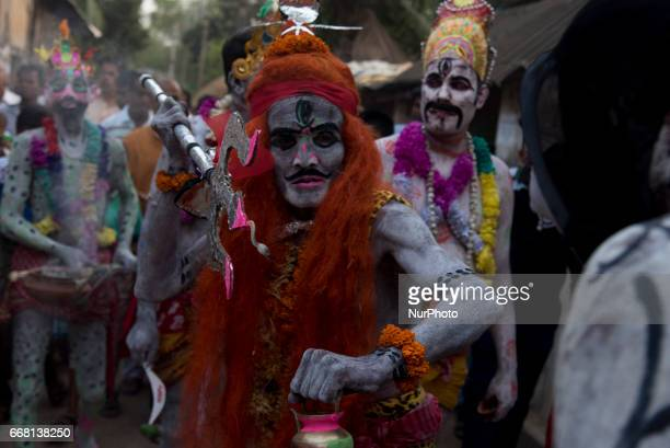 A soung of gajan is performing in the avatar of lord shiva while the other soungs are watching his acts in Burdwan India on 13 April 2017...
