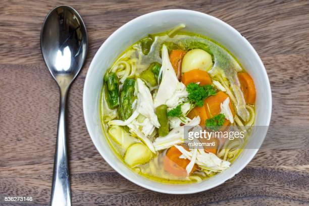 Soup bowl of chicken with noodles, carrots, asparagus, garlic and soy sauce