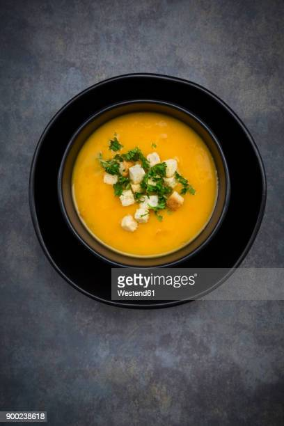 Soup dish of creamed pumpkin soup with croutons and parsley
