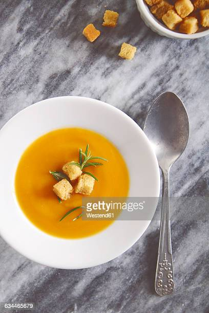 Soup dish of creamed pumpkin soup with croutons and rosemary