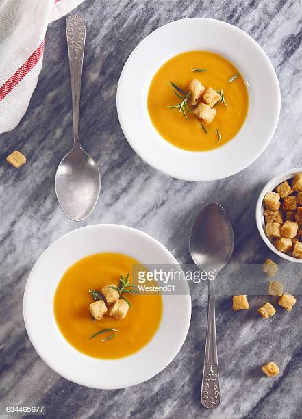 Soup dishes of creamed pumpkin soup with croutons and rosemary