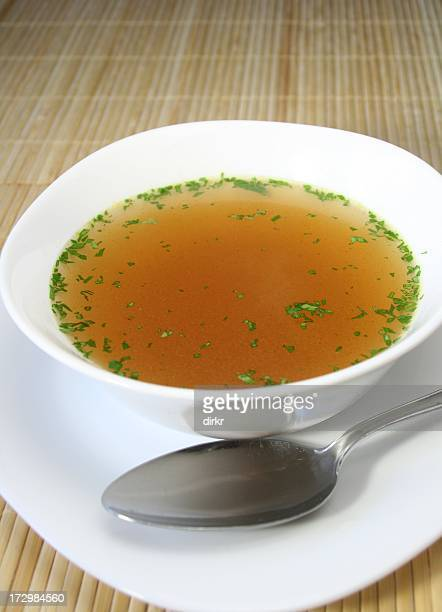 Soup in a white bowl with a silver spoon on the side