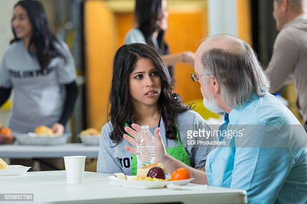 a soup kitchen working speaking to a person in need. - depression bread line stock pictures, royalty-free photos & images