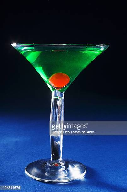A sour apple martini on a blue background.