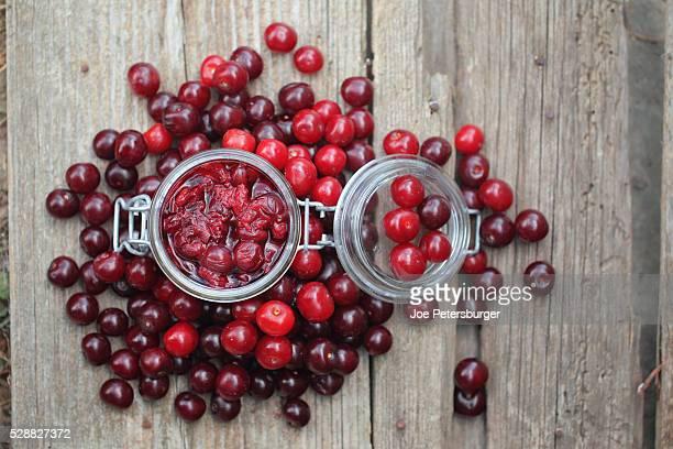 sour cherry chutney in a jar with fresh cherries around. - サワーチェリー ストックフォトと画像