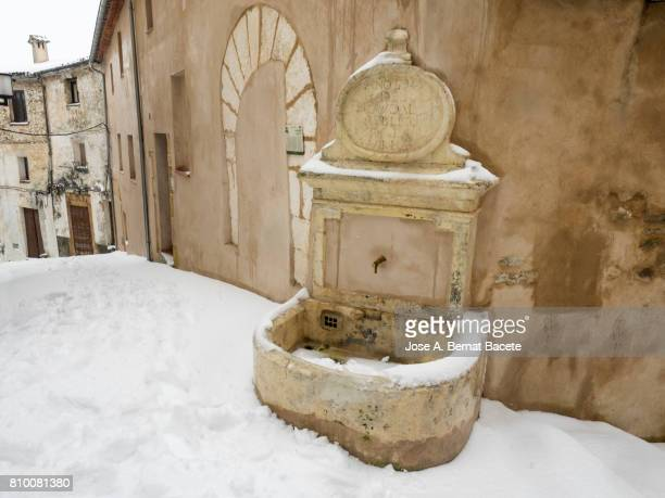 Source of ancient water carved in stone in the street of a former people of medieval architecture, in winter with snow in the street. Bocairent, Valencia, Spain.