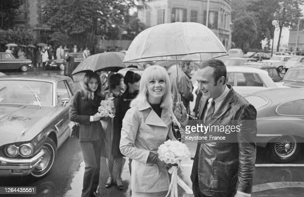 Souriants sous un parapluie Mylène Demongeot et son mari Marc Simenon sourient devant les caméras à SaintCloud France le 16 septembre 1968