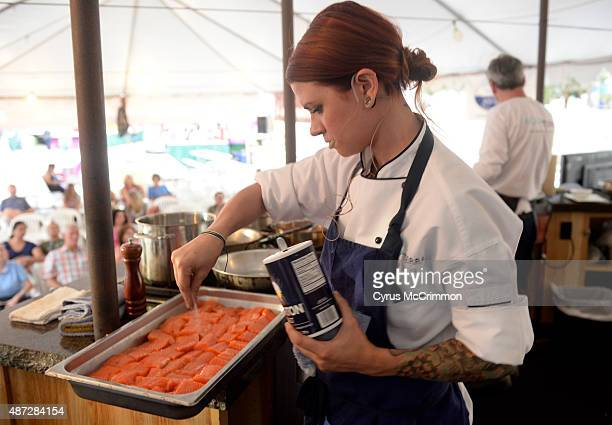 Sous Chef Pippa Taylor of Baur's restaurant in Denver salts the Arctic Char as she does a culinary demonstration at A Taste of Colorado Festival on...