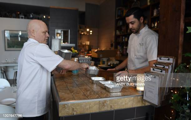 Sous chef Robbie Probert and owner Campbell Mickel lay out takeaway trays as they start to prepare dishes from their 'Social Distancing Menu' to be...