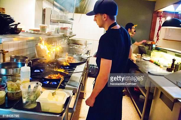 Sous-chef cuisinier sauteeing panful de chanterelles champignons