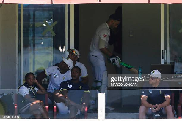 South Africa bowler Kagiso Rabada sits in the players stand as South Africa batsman and captain Faf du Plessis warms up during day four of the second...