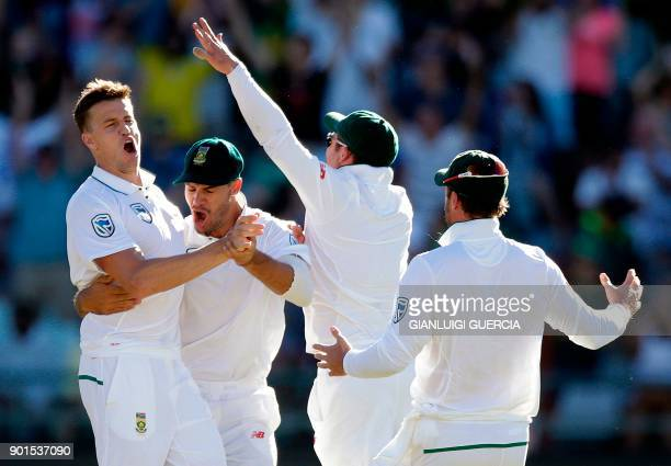 South Africa bowler Morne Morkel is congratulated by teammates after dismissing unseen Indian batsman Virat Kohli during the first day of the first...
