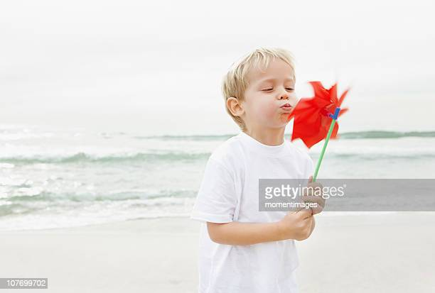 South Africa, Boy (4-5) blowing on red pinwheel