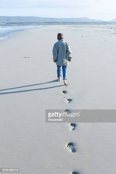 South Africa, Cape Town, back view of a boy walking on the beach