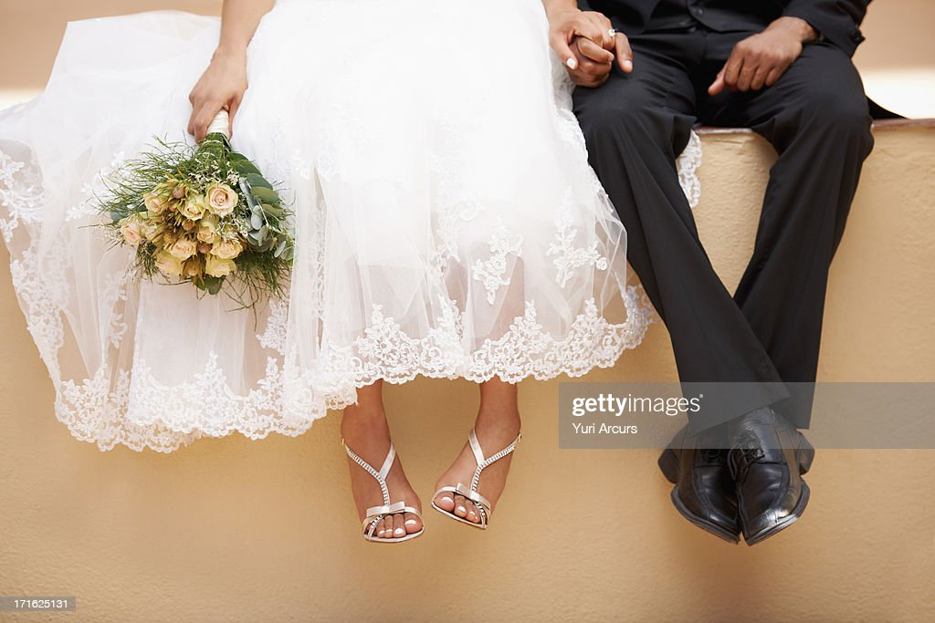 South Africa, Cape Town, Bride and groom sitting on wall : Stock Photo