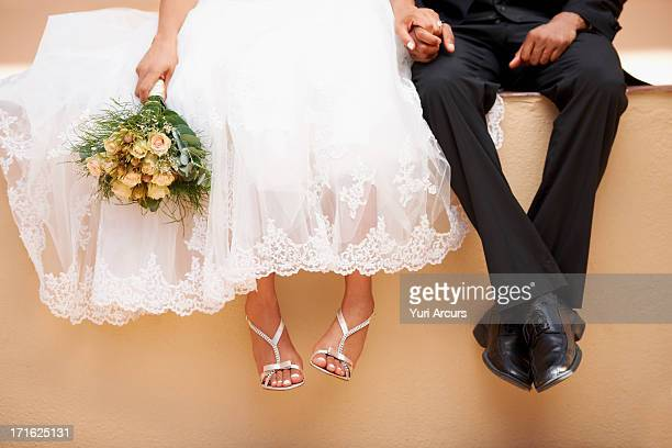 South Africa, Cape Town, Bride and groom sitting on wall