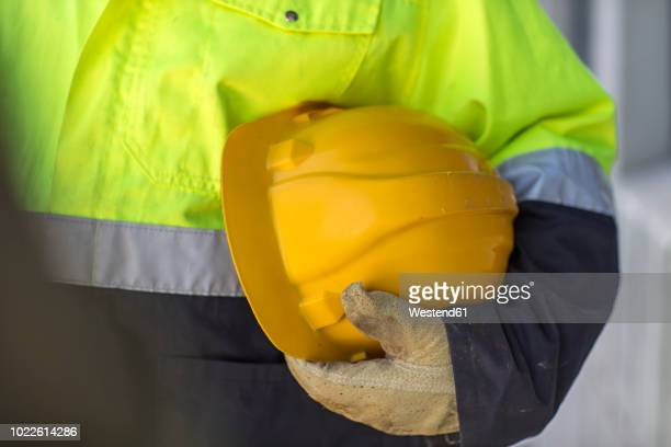 south africa, cape town, builder holding hard hat - reflective clothing stock pictures, royalty-free photos & images