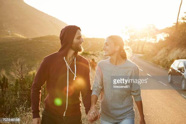 South Africa, Cape Town, happy young couple walking hand in hand at roadside
